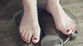 Weibliche Stellung auf Gewichts-Skala Video 3840X2160 UHD stock footage