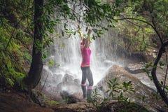 Weibliche Stellung in den Wasserfällen mit üppigen Farnen, Bäume im bushland lizenzfreies stockfoto