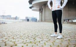 Weibliche Stellung der Eignung auf Bürgersteig in der Stadt lizenzfreies stockfoto