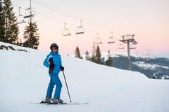 Weibliche Stellung des glücklichen Skifahrers in den schneebedeckten Bergen, die Winterurlaube genießen Stockbilder