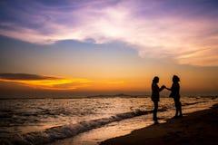Weibliche Stellung des Schattenbildes auf dem Sonnenuntergangstrand Stockbilder