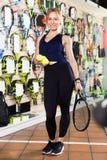 Weibliche Stellung im Sportwarenladen mit Bällen und Schläger stockbilder