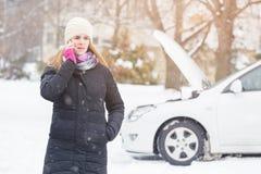 Weibliche Stellung nahe bei defektem Auto und Unterhaltung am Handy stockbild