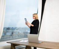 Weibliche stolze lesende Börsennachrichten CEOs im Internet über tragbare Notenauflage stockfotografie