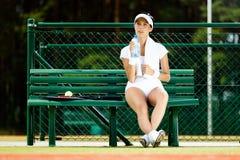Weibliche Tennisspielerreste an der Bank Lizenzfreie Stockfotografie