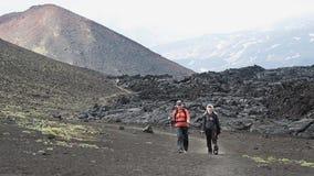 Weibliche Touristen, die auf Spur auf Hintergrund des Lavaflusses und Kegel des Vulkans gehen stock footage
