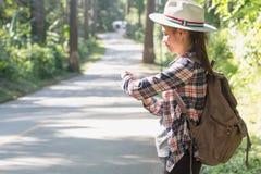 Weibliche Touristen mit Rucksäcken warten auf Busse in der Landschaft mit Bäumen und schöner Natur stockfotos