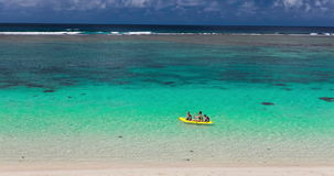 Weibliche und kleine Jungen, die Kanu auf einer tropischen Lagune schaufeln stock footage
