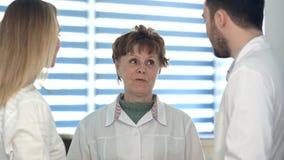Weibliche und männliche Doktoren, die mit einer älteren Krankenschwester sprechen lizenzfreie stockfotografie