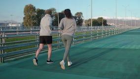 Weibliche und männliche Läufer bilden auf offenem Stadion, hintere Ansicht aus stock video