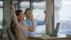 Weibliche und männliche Mitarbeiter, die E-Mail auf Laptop lesen und extrem glücklich werden stock video