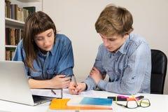 Weibliche und männliche Studenten, die auf einer Schule oder einer Arbeitsvorgabe mit-arbeiten lizenzfreies stockbild