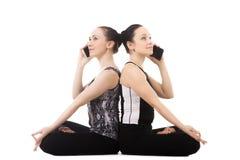 Weibliche Unterhaltung von zwei Jogi am Handy im Yoga Lotus Pose Lizenzfreie Stockbilder
