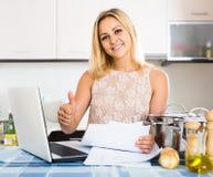 Weibliche unterzeichnende Dokumente an der Küche Lizenzfreies Stockfoto