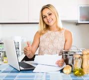 Weibliche unterzeichnende Dokumente an der Küche Stockfotos