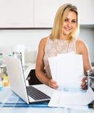 Weibliche unterzeichnende Dokumente an der Küche Lizenzfreie Stockfotos