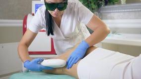 Weibliche Verfahren, Service-Personal in medizinische Gläser tut Enthaarung auf Beinen der Kundenfrau, die herein Laser-Apparat v stock footage