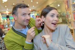Weibliche versuchende Ohrringe im Einzelhandelsgeschäft lizenzfreie stockfotografie