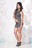 Weibliche vorbildliche Aufstellung mit einem Ballonhintergrund Stockfoto
