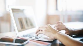 Weibliche weiße Hände auf einem Schreibenc$simsen der Aluminiumlaptoptastatur stockfotos