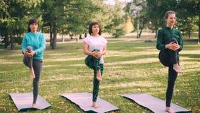 Weibliche Yogastudenten tun die balancierende Übung, die auf einem Bein auf Matten im Park steht, Mädchen ausbilden unter Anleitu stock footage