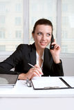 Weibliche Zeichen dokumentiert das Sitzen am Tisch und die Unterhaltung am Telefon Stockfoto