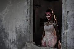 Weibliche Zombieleichenstellung vor Schmutzwand in verlassenem Haus Grausigkeit und Geistkonzept Halloween-Tagesfestival und stockbilder