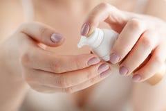 Weibliche zutreffende Feuchtigkeitscreme zu ihren Händen nach Bad Skincare Co lizenzfreies stockbild