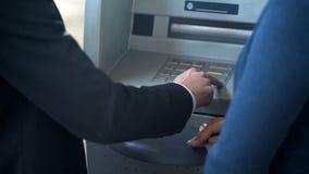Weiblichem neuem Kunden des Bankangestellten, zeigend, wie man mit ATM, guter Service arbeitet lizenzfreie stockfotos