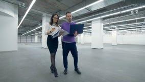 Weiblichen und Spezialisten einer männlichen Architektur gehen entlang das Gebäude stock footage