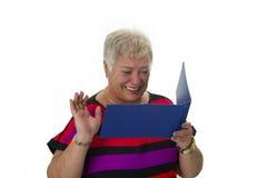 Weiblicher älterer schauender Kontoauszug stockfotografie