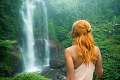 Weiblicher Abenteurer, der Wasserfall betrachtet Stockbild