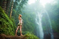 Weiblicher Abenteurer, der Wasserfall betrachtet Lizenzfreie Stockbilder