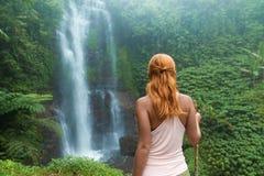 Weiblicher Abenteurer, der Wasserfall betrachtet Stockfotografie