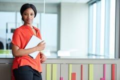 Weiblicher afrikanischer Unternehmer, der eine Tablette beim Betrachten der Kamera holdiing ist Lizenzfreie Stockfotos