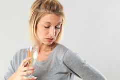 Weiblicher Alkoholismus für die junge blonde Frau, die sprudelnden Wein hält Lizenzfreie Stockfotos