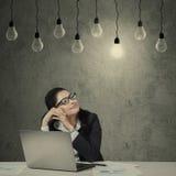 Weiblicher Angestellter mit dem Laptop, der Glühlampe betrachtet lizenzfreies stockbild