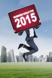 Weiblicher Angestellter springt mit Unternehmenszielen für 2015 Lizenzfreies Stockfoto