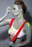 Weiblicher Anstreicher bespritzte mit Latex-Farbe Stockfoto