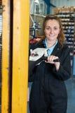 Weiblicher Arbeiter-Using Powered Fork-Aufzug, zum von Waren zu laden Stockfotos