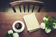 Weiblicher Arbeitsplatz Blogger mit Schale schwarzem Kaffee, Anmerkung über Arbeitsholztisch Weinleseart und Draufsicht Süßes Hör Stockfoto