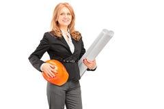 Weiblicher Architekt, der einen Plan und einen Sturzhelm hält Stockbilder