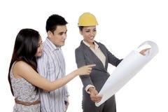 Weiblicher Architekt, der ihrem Kunden einen Plan zeigt Stockfotos