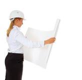 Weiblicher Architekt, der Lichtpause überprüft stockfotografie