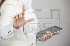 Weiblicher Architekt, der mit einer virtuellen Wohnung arbeitet Stockfotografie