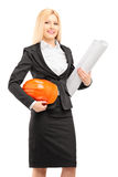 Weiblicher Architekt im schwarzen Anzug, der einen Sturzhelm und einen Plan hält Stockfotografie