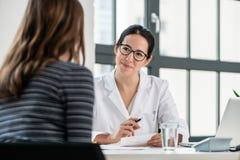 Weiblicher Arzt, der auf ihren Patienten während der Beratung hört Stockbild