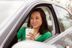 Weiblicher asiatischer Fahrer, der Mitnehmergetränk in einem Auto trinkt lizenzfreies stockfoto
