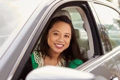 Weiblicher asiatischer Fahrer, der zur Kamera durch Seitenfenster schaut stockfotos