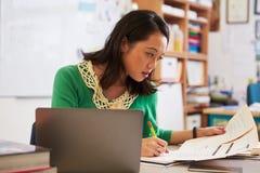 Weiblicher asiatischer Lehrer bei ihrer Schreibtischmarkierung studentsï ¿ ½ Arbeit stockfotografie